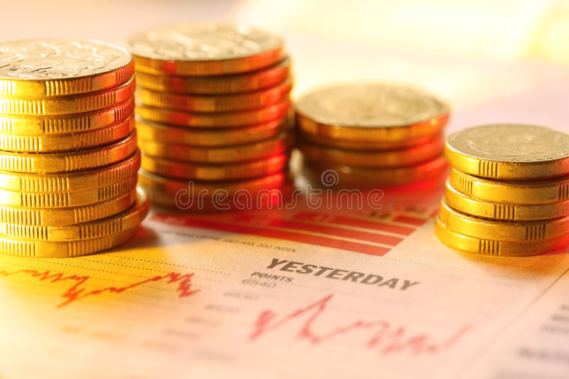 Coins on Graph. Stacks of gold coins on a newspaper finance graph. Warm tones, shallow depth of field royalty free stock photo