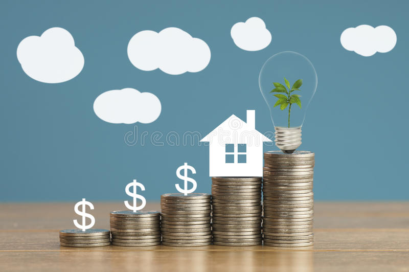 coins and house paper with green small tree, light bulb on money, concept in save, finance and grow of business about home stock image