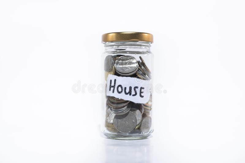 Coins in a jar with a note written ` HOUSE `. on a white background. Saving money to buy house. free copy space. Saving concept. Malaysia currency royalty free stock photography