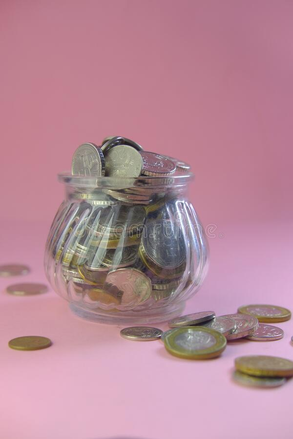 Coins in a jar on pink background, close up.  royalty free stock photo
