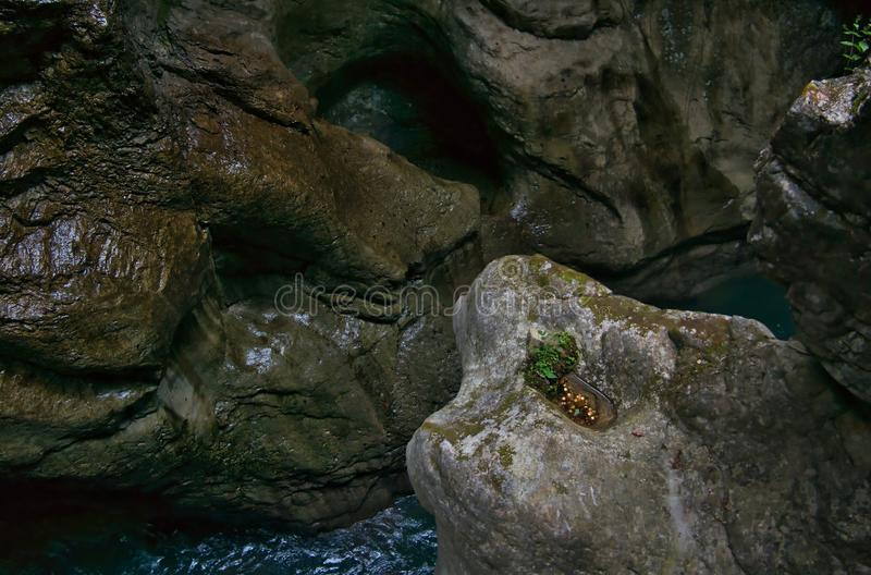 Coins on a ledge in a gorge. Smooth and shiny stones in a ravine with coins on a ledge royalty free stock photography