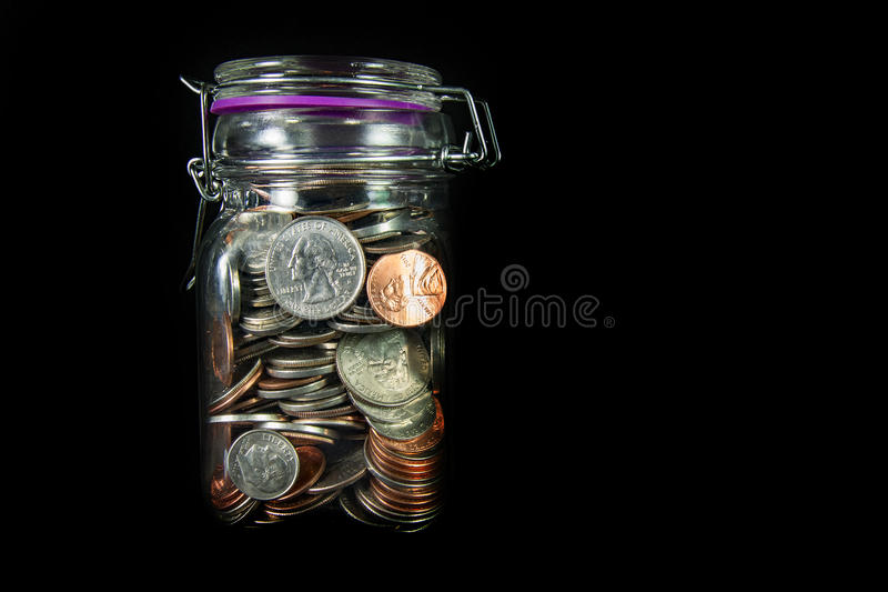Coins in a Mason Jar. A horizontal view of American coins in a glass mason jar on a black background with space for text at the right royalty free stock images