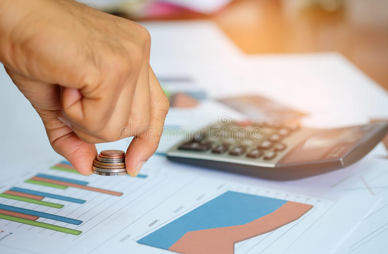 Coins in men`s hands are using the cost analysis calculator. stock photography