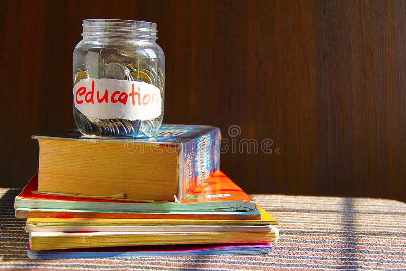 Coins in money jar with education label royalty free stock photo