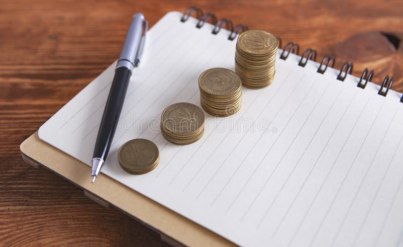 Coins notebook pen.  royalty free stock image