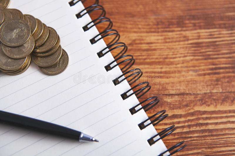 Coins notebook pen.  royalty free stock images