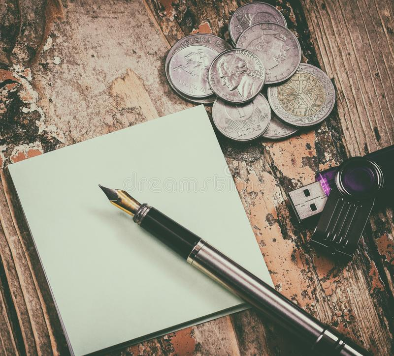 Coins, pen. Creative multi-coin image and pen with paper for recordings on old wooden surface stock photo