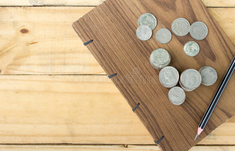 Coins and Pencil on handmade book on wood table royalty free stock photo