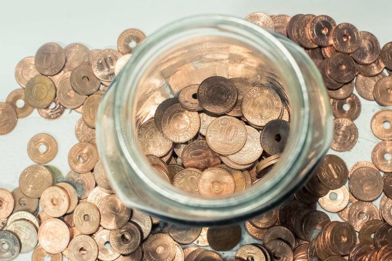 Coins placed on glass jar. And coins scattered around the glass jar stock photography