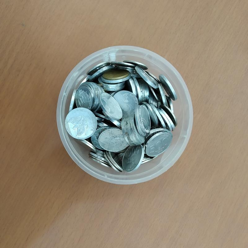 Coins in a plastic bowl royalty free stock photography