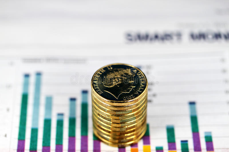 Coins of the realm. Some gold coins stacked on a newspaper graph where the trend is down, indicating that the stock market is on the verge of collapsing royalty free stock images