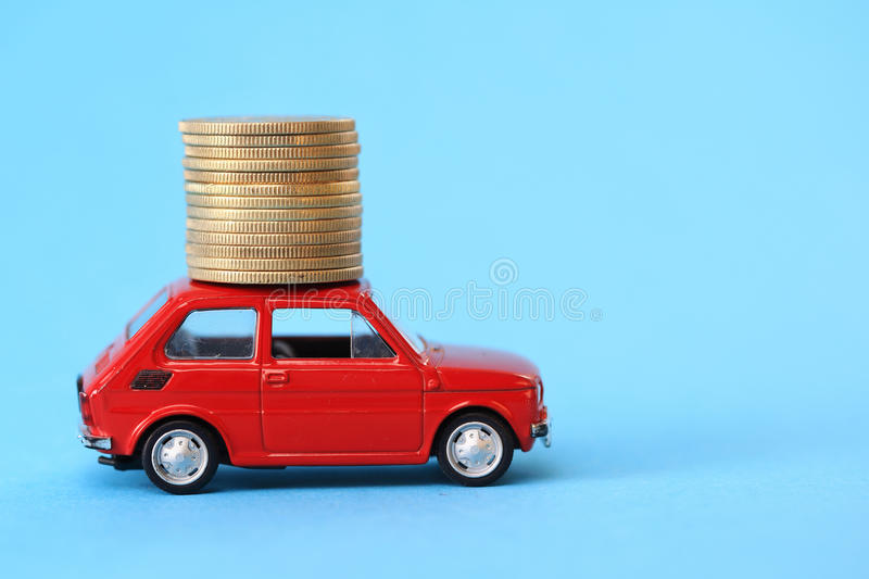 Coins on red miniature car. Coin stack on red miniature car royalty free stock image