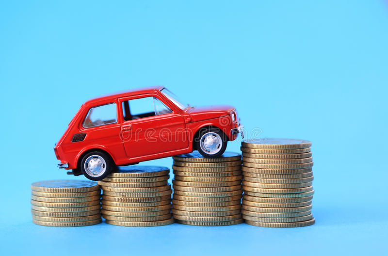 Coins on red miniature car. Coin stack on red miniature car stock photography