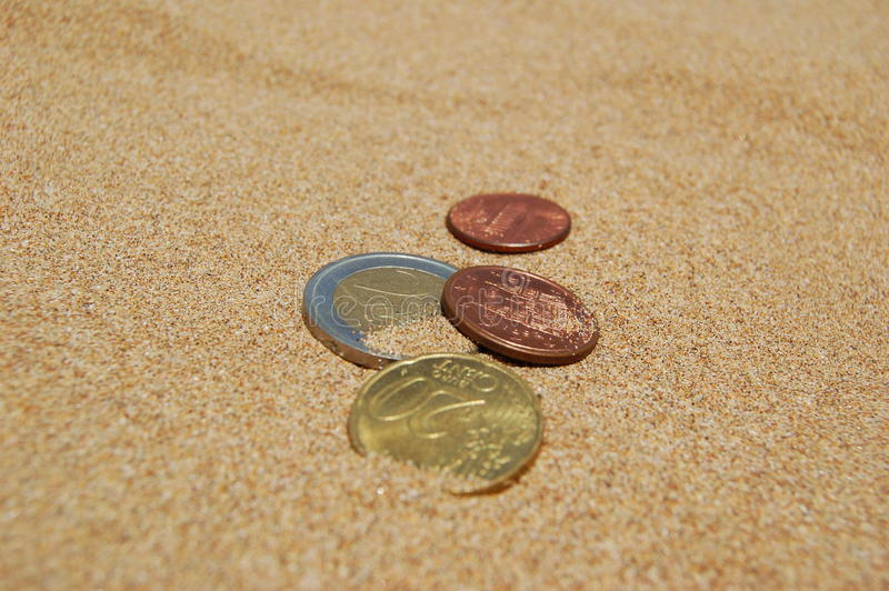 Coins in sand stock photography
