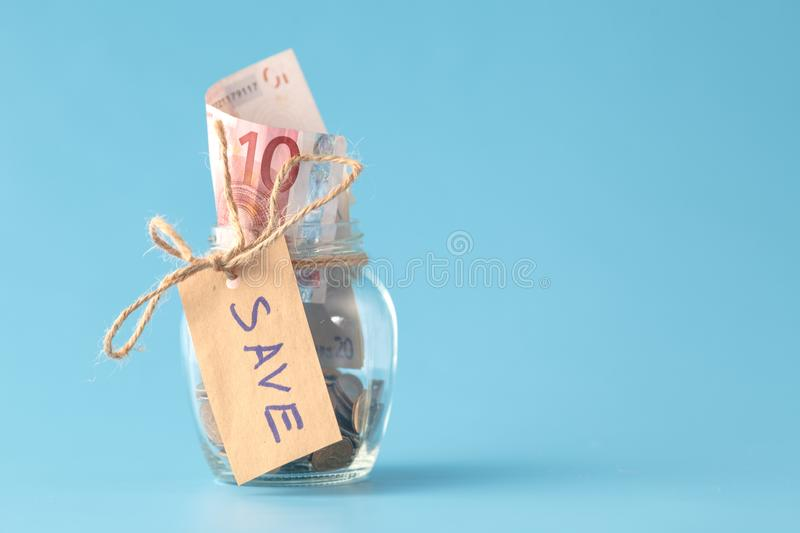 Coins in savings jar full of money stock photos