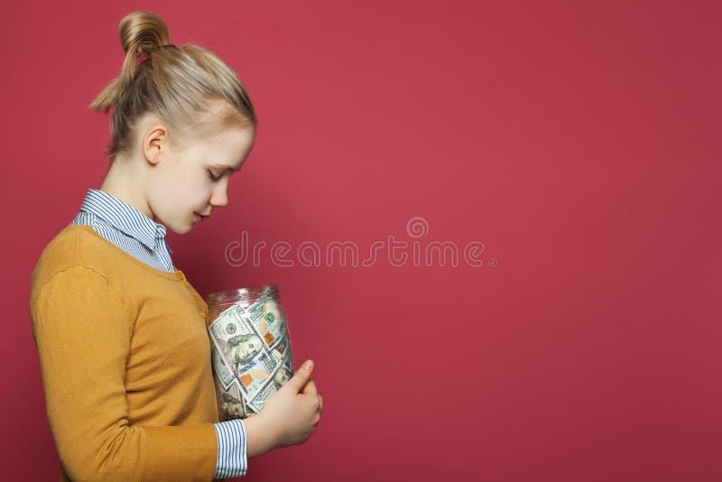 coins sparande f?r stapel f?r begreppshandpengar skyddande Nätt ung flicka som rymmer pengarkassa royaltyfri bild