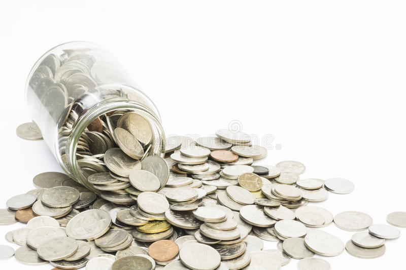 Coins spilling from a money jar. Isolated coins spilling from a money jar royalty free stock photo