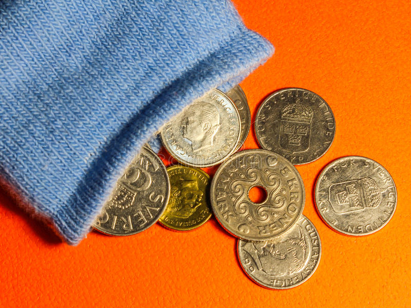 Coins spilling out from a blue sock royalty free stock photo