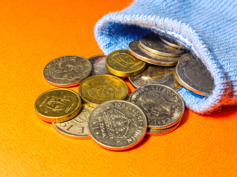 Coins spilling out from a blue sock royalty free stock images