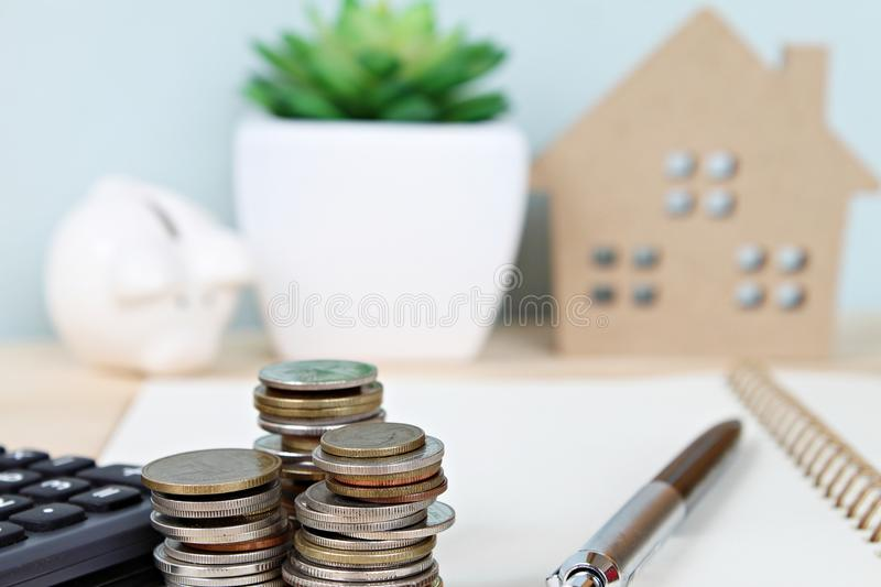 Coins stack and calculator in front of wood house model and piggy bank on office desk table stock image