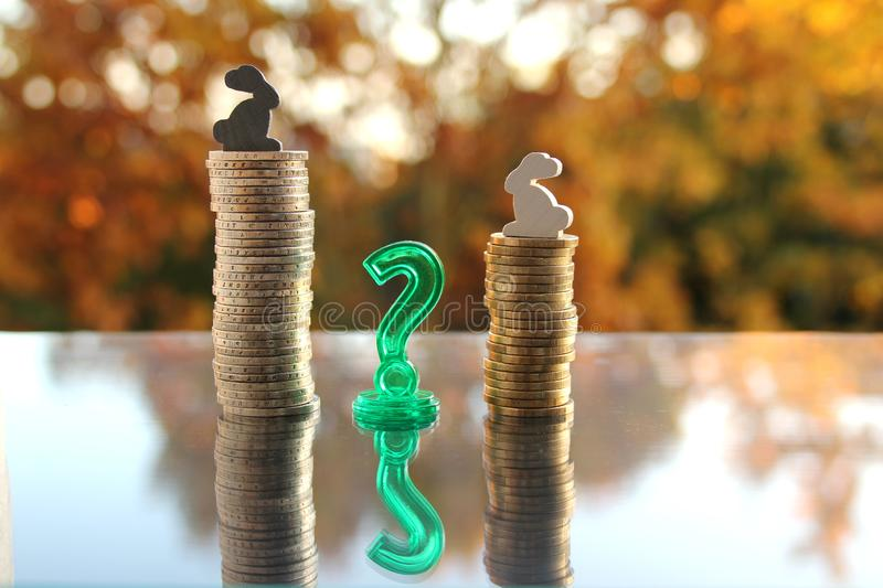 Coins stack of cash of the European Union with a model of colored bunnies on a blurred background autumn landscape in the. Backlight, the concept of a white royalty free stock image