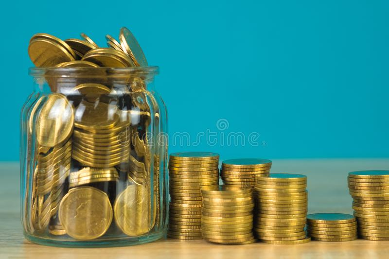 Coins stacks and gold coin money in the glass jar on table with green background, for saving for the future banking finance stock image