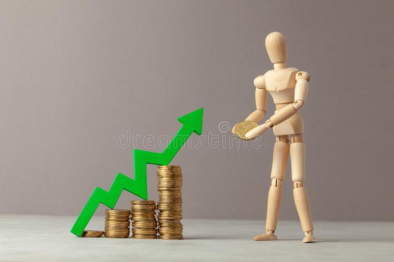 Coins stair up and arrow up graphics. A businessman carries a coin making an investment. Business profit growth. Coins stair up and arrow up graphics. A stock photography