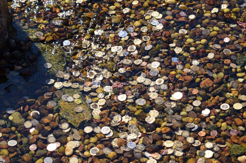 Coins thrown into the water in a fountain for luck.  stock image