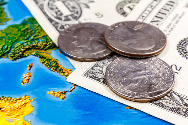 Coins with US dollars banknotes on the background of geographic map. Travel concept royalty free stock photos