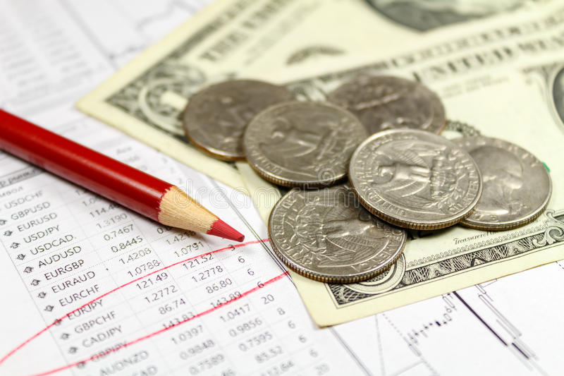 Coins with US dollars banknotes and red pencil on the background of table of exchange rates. Focus on the pencil stock image