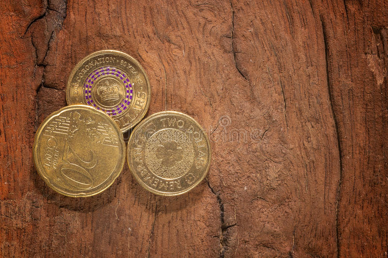 Coins on wood. Euro And Australian currency coins on wood background stock photo