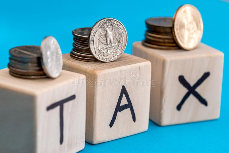 Coins with wooden cubes and text of tax. concept time royalty free stock photo