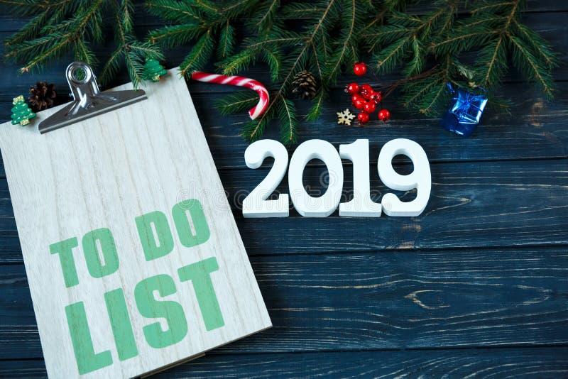 Cojín de madera con la decoración, ramas de la picea y taza de café roja en la tabla de madera gris Decoración del Año Nuevo y de fotos de archivo libres de regalías