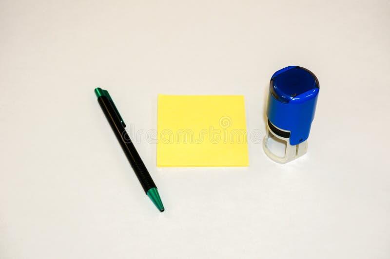Cojín de nota pegajoso amarillo, sello de goma redondo y pluma fotos de archivo libres de regalías