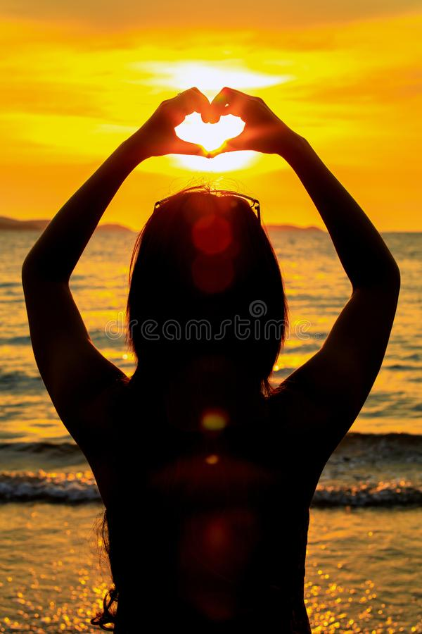 Coja el sol a mano con forma del corazón en tiempo de la puesta del sol en el mar y la isla imagen de archivo libre de regalías