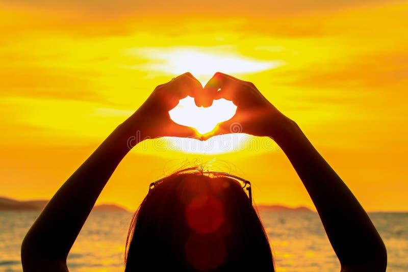 Coja el sol a mano con forma del corazón en tiempo de la puesta del sol en el mar y la isla fotografía de archivo libre de regalías