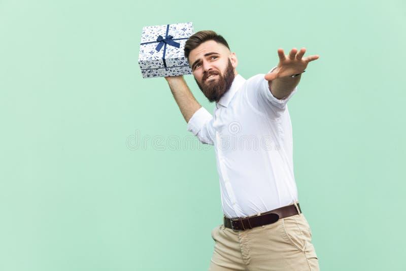¡Coja su regalo! El hombre adulto joven balanceó y quiere lanzar de su caja de regalo, aislada en fondo verde claro imagen de archivo