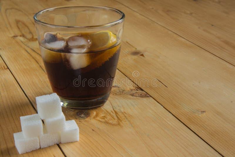 Coke con ghiaccio ed il limone con il cubo dello zucchero immagini stock libere da diritti