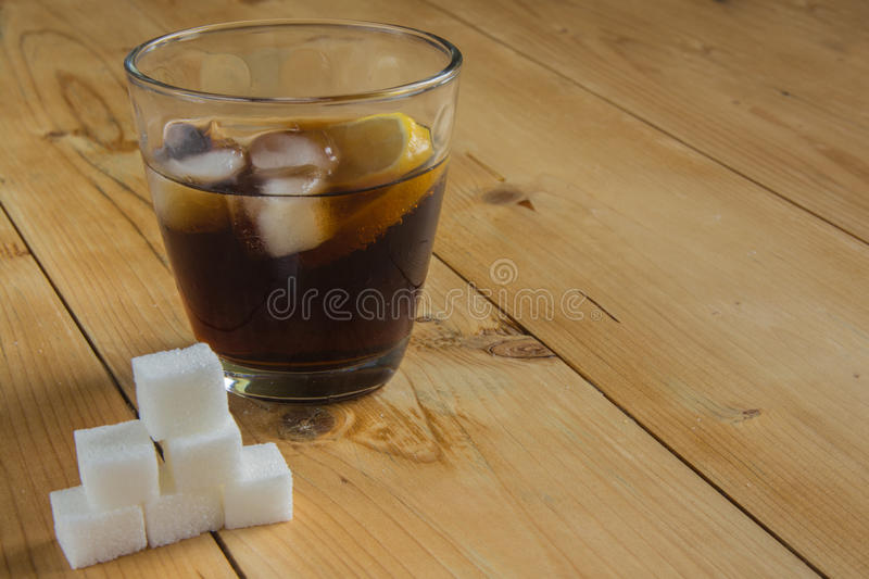 Coke with ice and lemon with sugar cube. Coke with ice and lemon on wood royalty free stock images