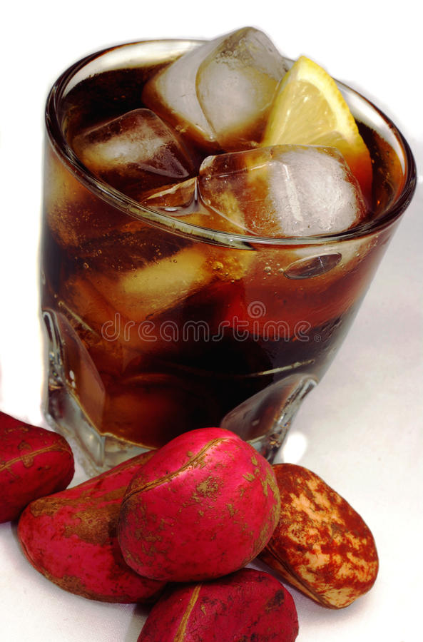Coke and kola nuts. A glass of cola with ice and lemon surrounded by fresh Kola Nuts stock images