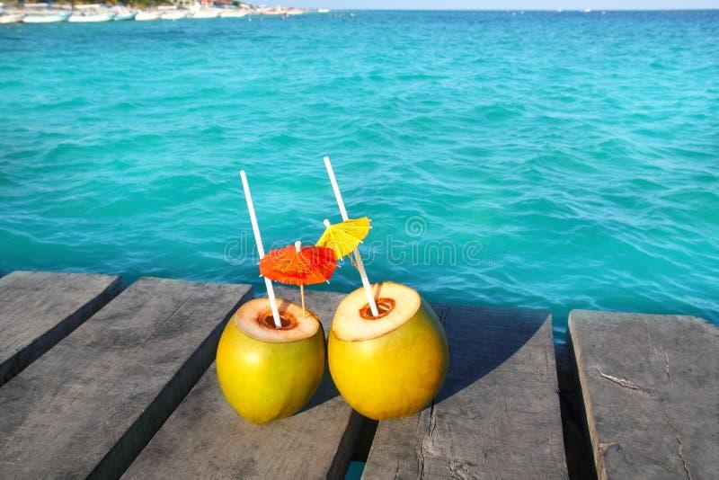 Coktails del coco en el Caribe en el embarcadero de madera imagen de archivo