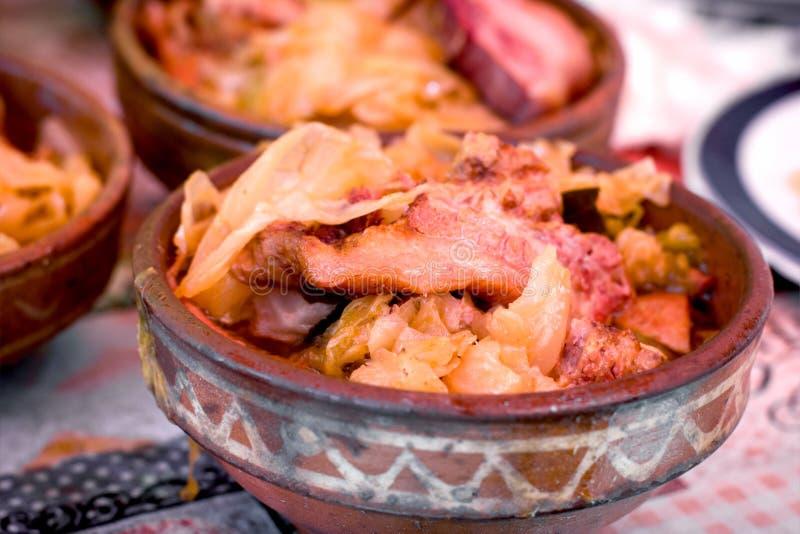 Col con la carne ahumada - chucrut con cerdo, carne de vaca de la ternera y el cordero en cuenco terroso foto de archivo