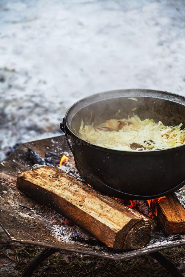 Col con la carne que cocina en una caldera en el fuego abierto foto de archivo