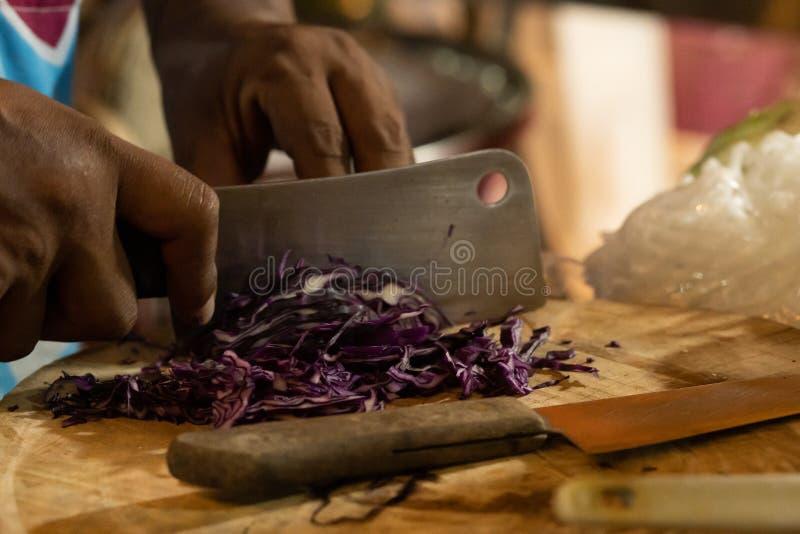 Col púrpura cortada en un tablero de madera con un cuchillo grande imagenes de archivo