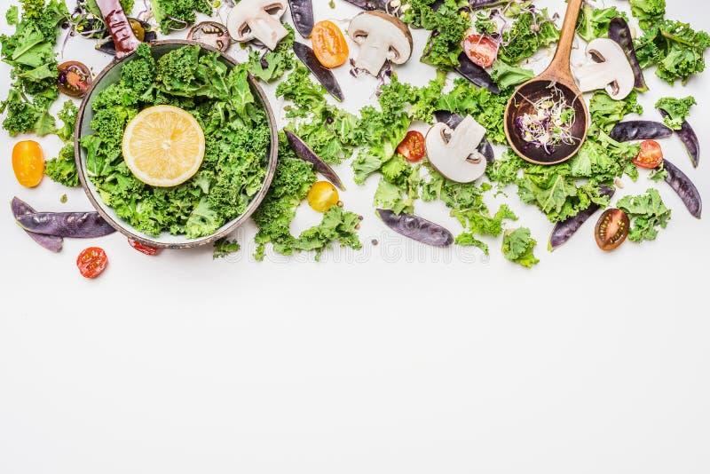 Col rizada fresca en cocinar el pote con los ingredientes de las verduras en el fondo de madera blanco, visión superior imagen de archivo libre de regalías