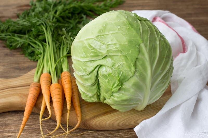Col y zanahorias jovenes frescas con los verdes para la ensalada de la ensalada de col foto de archivo libre de regalías