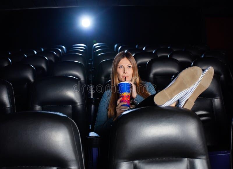 Cola bebendo da mulher relaxado ao olhar o filme fotografia de stock
