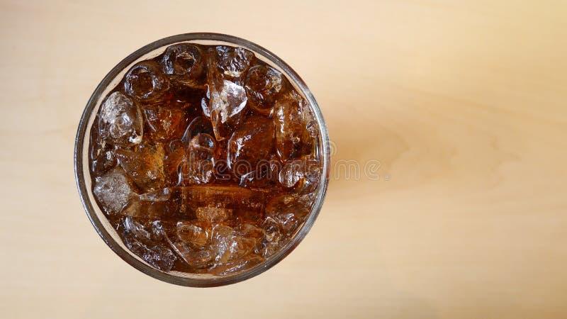 Cola con los cubos de hielo en la opinión superior de cristal sobre el fondo de madera de la tabla imagenes de archivo