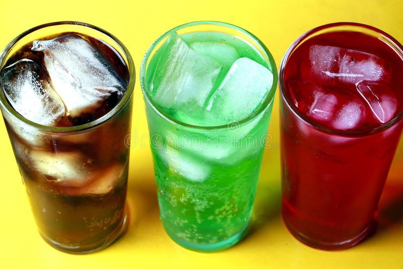 Cola, creme soda and raspberry soda fizzy drinks. Red, green and cola soda fizzy drinks in glasses with ice on a yellow background royalty free stock photos