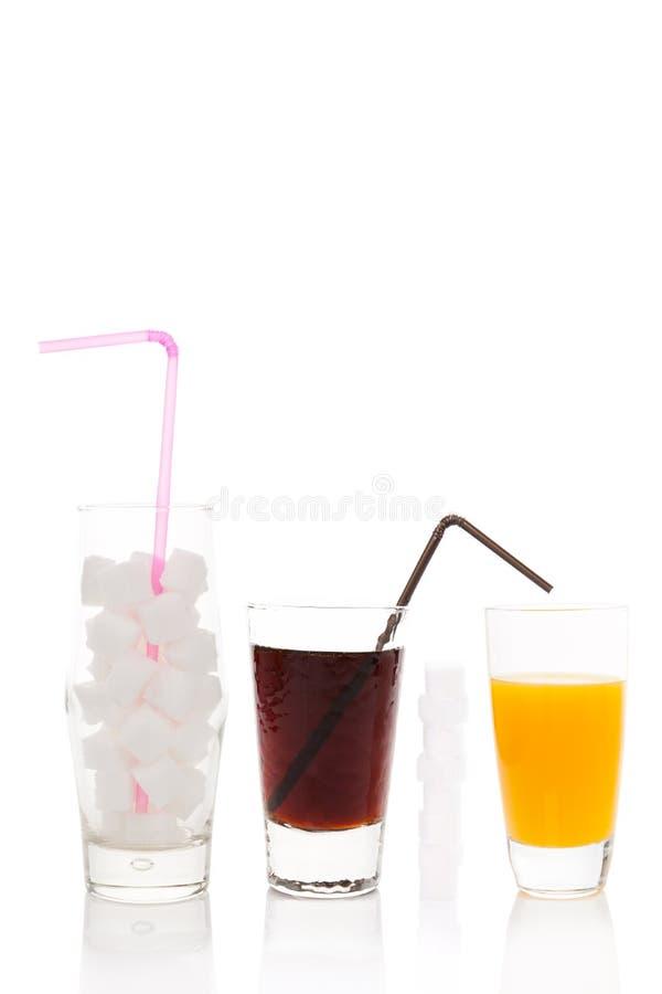 Cola, cubos do açúcar e suco de laranja no vidro fotos de stock